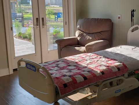 a quilt-covered hospital bed beside french doors