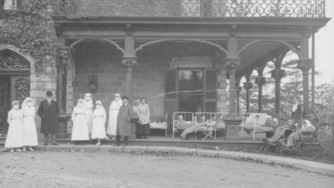 black and white photo of nurses standing in front of a building