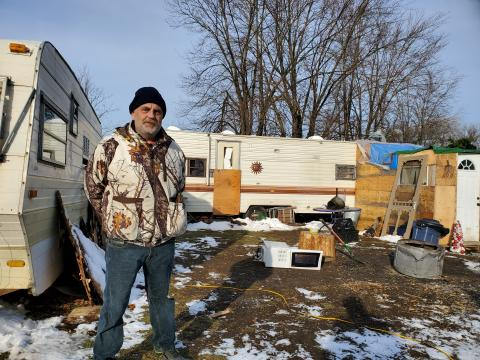 Man stands in front of trailers