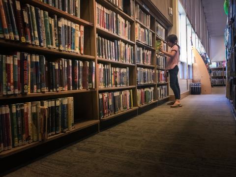 Girl looks at bookshelves in library.