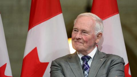 a white-haired man in a suit stands in front of Canadian flags