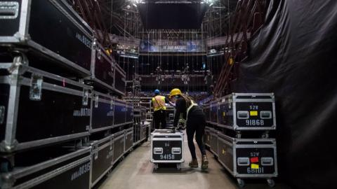 workers loading music equipment into a venue