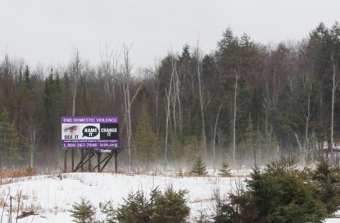 a billboard in front of a forest