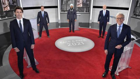 five men in suits stand on a red rug