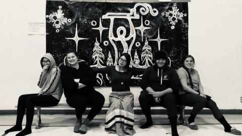 a group of people sitting in front of a mural