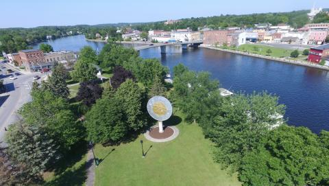 overhead shot of a giant coin in front of trees and water