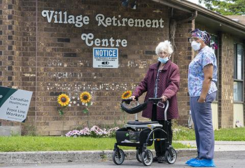 A resident and a worker at Orchard Villa Long-Term Care in Pickering