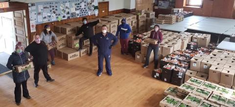 Workers stand in front of crates of food