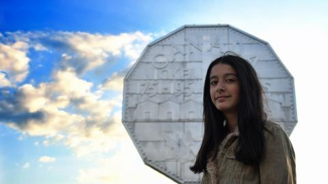 long-haired girl standing in front of a giant nickel
