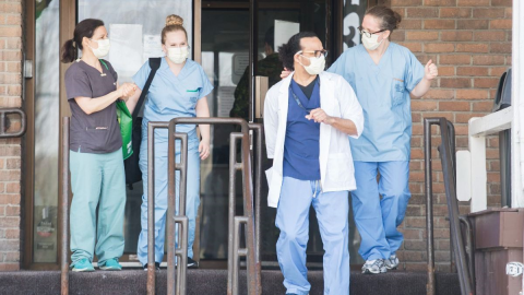 People wearing hospital scrubs and masks exit a building.