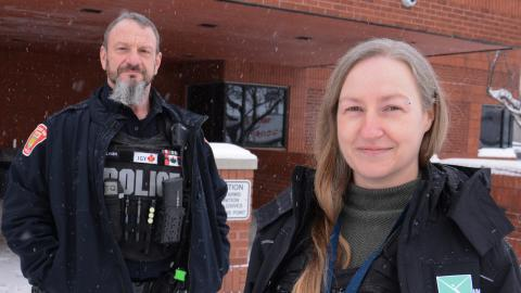 a bearded police officer stands next to a smiling, long-haired woman