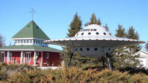 large model of a flying saucer outside a red and white building