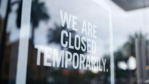 window sign saying, we are temporarily closed