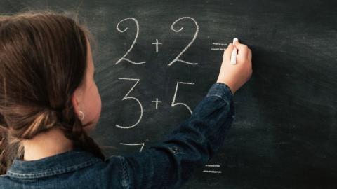 child doing arithmetic on a blackboard