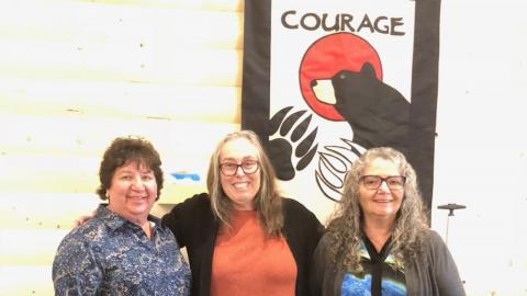 "three smiling women stand in front of a sign reading ""courage"""