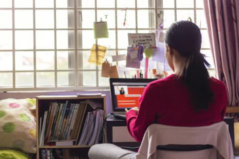 a woman sits by a window using her laptop
