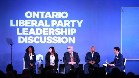 Steve Paikin and five liberal leadership candidates sit on a stage during a debate