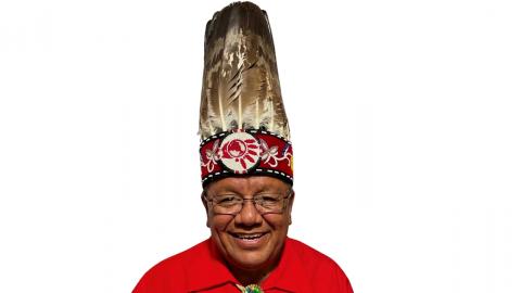 man in red shirt wearing a tall headdress
