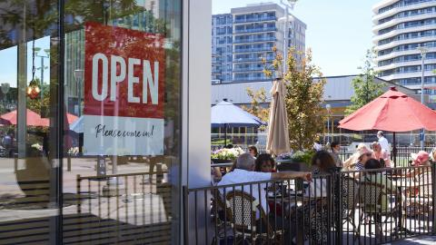 """people sit on a patio next to a business with an """"open"""" sign"""