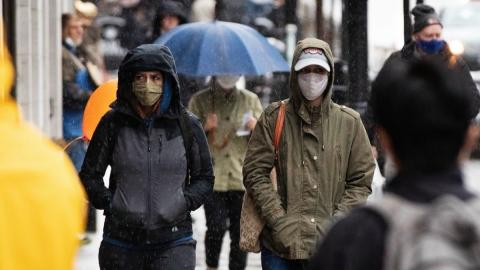 People walk on a crowded sidewalk wearing masks.