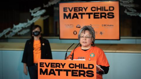 """woman in orange shirt stands with banners reading """"Every Child Matters"""""""
