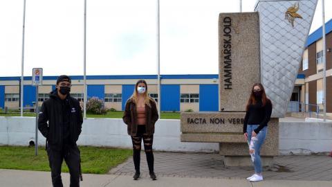 three masked students stand in front of a high school
