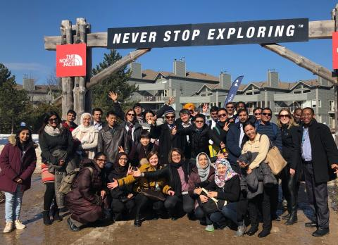 "a group of people stand in front of a sign that reads ""never stop exploring"""