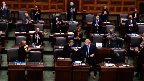 People in Ontario legislature stand and applaud as one man shakes another man's hand in the centre of the picture.