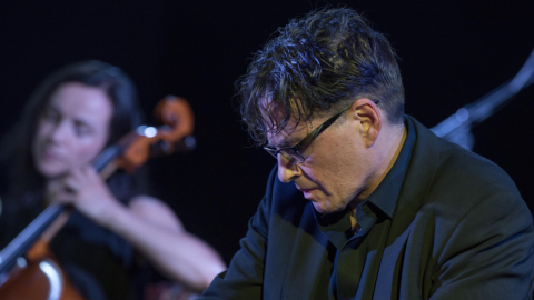 closeup of man in glasses with woman playing cello in the background