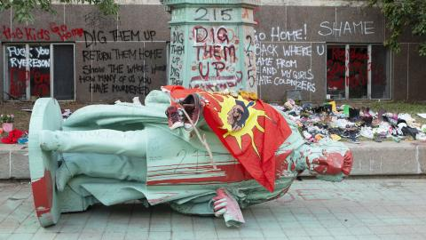 a statue lies on the crowd, covered in red paint and draped with a red flag