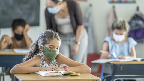masked children sit at desks in a classroom