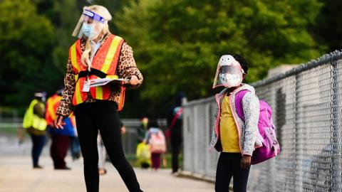 Teacher and student stand on a sidewalk, wearing personal protective equipment.