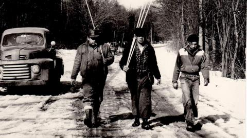 black and white photo of three men walking down a snow track carrying wood