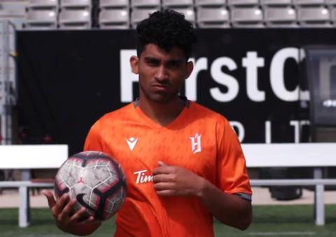 Man in soccer jersey, holding soccer ball.