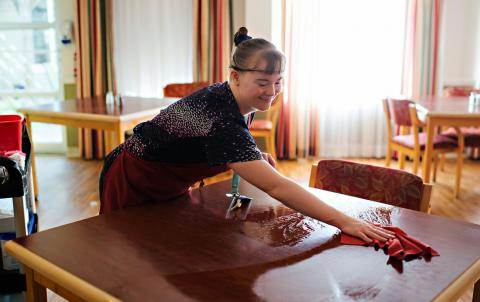 a woman cleaning a table in a restaurant