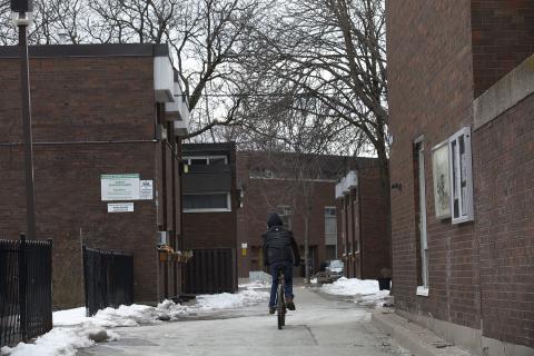 a person riding a bike into a housing development