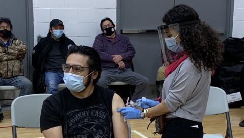 a masked man receiving a shot