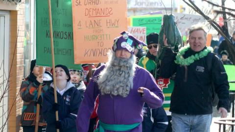 a man in a purple outfit known as St. Urho leads a parade in Thunder Bay