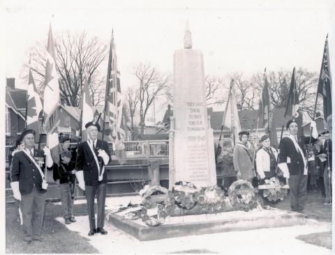 uniformed men stand beside a cenotaph
