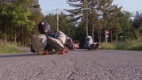 Two people in helmets riding street luge sleds on a roadway.