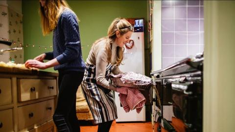 Two women in a kitchen. One pulls a dish covered with foil out of the oven.