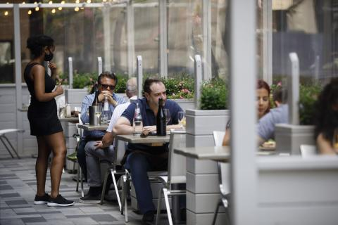 a masked server with customers on a patio