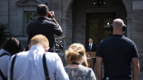 a group of media standing in front of Justin Trudeau
