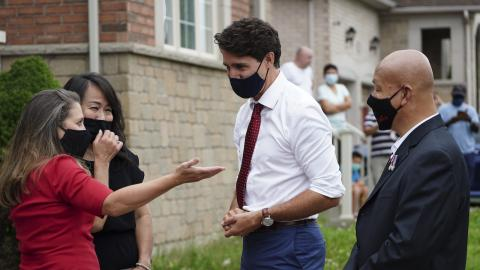 two women and two men stand outside in masks