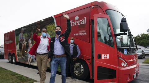 two men wave in front of a red bus
