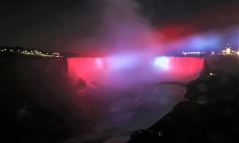 Niagara Falls at night lit up in red.