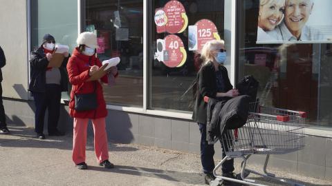 two masked women wait on the sidewalk outside a store