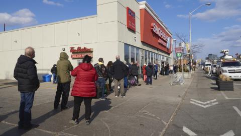 people lined up outside a drug store
