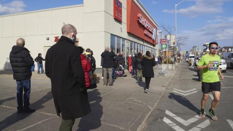 people line up outside a pharmacy as a jogger runs past