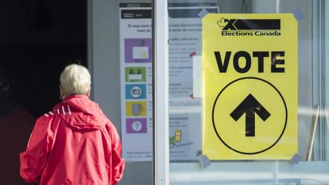 """person in a red coat waling past a yellow sign that reads """"vote"""""""